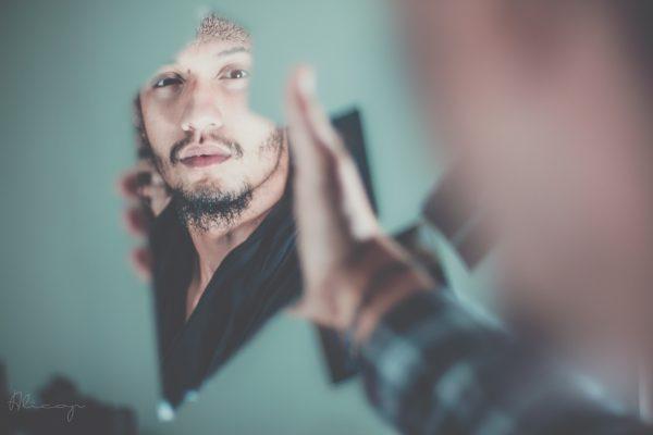 man looking into broken mirror
